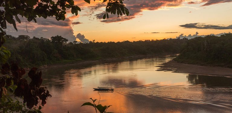 A view of a boat sailing on the Tambopata river