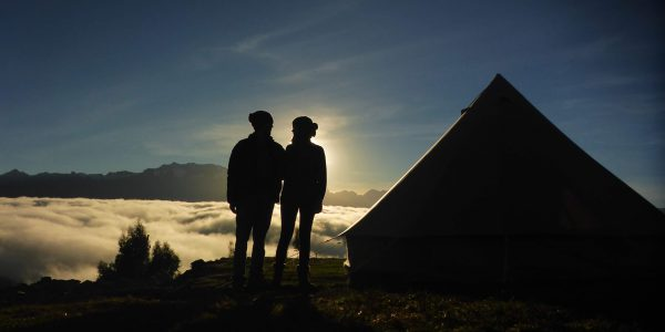 A couple enjoying the sunrise from their glamping tent in the Sacred Valley of the Incas