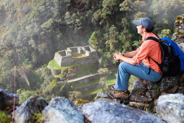 Explorer enjoying the view of Machu Picchu from above before arriving to the citadel