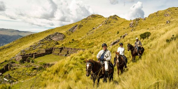 A group of people horseback riding around the Cusco outskirts